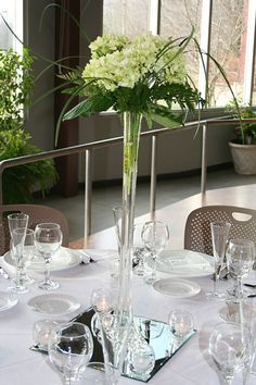 simple centerpiece, eiffle tower vase  Hydrangeas –  Green hydrangeas with leather leaf fern, lily grass and salal tips displayed in an elegant Eiffel tower vase, set on a beveled edge mirror with 4 votive candles.