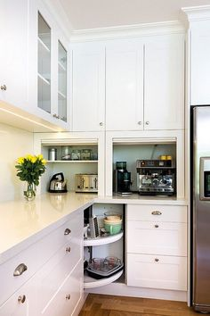 Small Kitchen Cabinet Plan.  Kitchen bin pulls, cabinet lazy susan, cake stand, cup pulls, glass front cabinets, glass backsplash, lazy susan, shaker style cabinet, stainless steel, tambour, white counters. Countertop is Caesarstone Snow. Kitchens by Peter Gill.