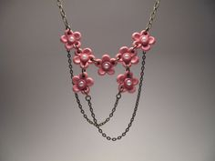This delicate cherry blossom necklace was hand-sculpted out of polymer clay with faux pearl centers. The flowers are 1/2 an inch each, and the connected pendant is 3 inches wide by 1-1/2 inches tall. It is attached to an antique brass chain, which ends in a matching lobster clasp and jump ring. The length of the necklace is 17 inches, with a 2-inch extender chain, allowing it to adjust up to 19 inches.