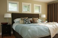 Put privacy film on windows above bed to filter light and stop the neighbors from peeking!