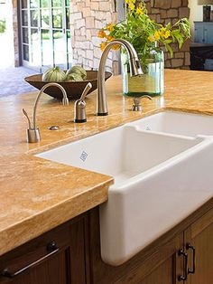 Middle Ground: Sink Area On the central island, a large farmhouse sink rests cozily amid granite countertops. The warm hues of the stone echo those featured in the nearby backsplash and in the home's rough-cut limestone walls. The plentiful counter space Double Kitchen Sink, Kitchen Island With Sink, Sink In Island, Kitchen Sink Design, Kitchen Island Decor, Kitchen Sink Faucets, Smart Kitchen, New Kitchen, Kitchen Ideas
