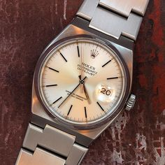 The Rolex Oysterquartz Datejust was introduced in the middle of the Swiss Quartz Crisis which nearly crippled the Swiss watch industry. Clearly inspired by Audemar Piguet's Gerald Genta-designed Royal Oak, the Oysterquartz models are attractive and collectible in their own right. This example from 1978, with a flat bezel, silver satin dial, bar markers, and baton hands, features the classic heavy-duty integrated Oysterquartz bracelet (Store Inventory# 9177, listed at $3600).  #rolex #quartz