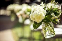 cream hydrangeas, yellow solidago, green maiden hair ferns, and green scented geranium in hanging mason jars