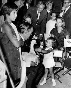 An original press photo from 1967 featuring Princess Stephanie, 2, daughter of Prince Rainer and Princess Grace of Monaco, patted a duck held by her father during a visit to a motion-picture set at Universal City Studio in Hollywood. At left is Princess Caroline, 10. Princess Grace, seated at right, worked formerly at the studio as Grace Kelly, movie star. The duck is used in the motion picture Jolly Pink Jungle.