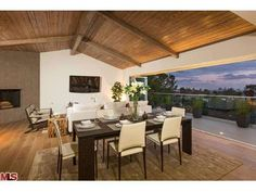 This Hollywood Hills dining room has wide plank wood flooring, an area rug, exposed beam wood flooring, built in fireplaces and wall of folding doors that open to the patio.