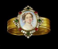 Gold, diamond, ruby and emerald miniature bracelet, the flexible band with centrepiece enclosing a portrait of Queen Victoria (1819-1901) wearing tiara on her head, earrings and pearls, flowers in her hair, facing three quarters front, within a diamond frame interspersed with four emeralds and four rubies. The back is inscribed MEINE THEUREN NICHTE STEFANIE VON VICTORIA RAM (9TEN MAI 1858) (MY DEAR NIECE STEPHANIE FROM VICTORIA R. (9 MAY 1858)). English.