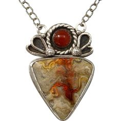Mexican Laguna Lace Agate Pendant Necklace  A gorgeous large freeform Mexican Laguna Lace cabochon set in sterling silver, is the focal point of this necklace. Laguna Lace Agate is an amazing stone with twists and turns of banding. This is an exceptional stone with oranges, peaches, creams, pinks, and dark reddish-orange. An orange carnelian has been paired with the agate while waves of silver surround the top of the pendant. This one-of-a-kind necklace measures 24 inches in length with a…