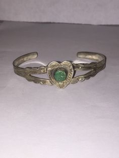 This is a beautiful, vintage Navajo Fred Harvey Era genuine green turquoise and sterling silver heart cuff bracelet that is handmade. …