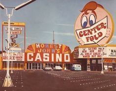 """Honest John's & Center-Fold. Las Vegas, 1975. The corner of the strip and Sahara Ave, where it was also known asBig Wheel and Jolly Trollybefore becoming Bonanza Gift Shop.Photorealist painting """"Honest John's Casino"""" (1976) by John Baeder."""
