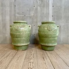 A pair of monumental Art Deco style terracotta jars by the Galloway Terracotta Company, c1920. Made to resemble antique Italian oil jars. Featuring stunning celadon colored mottled and crackled glaze. Molded lips and handles and applied rosettes on one side. Beautiful decorative objects fit for display inside or outside. Some chipping present near base and edges. Measurements: 21″dia. x 29″H (jar opening approx. 12″)