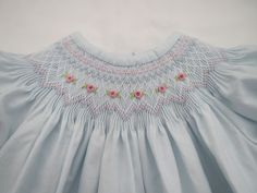A gorgeous smocking design including colors of pastel pink, blue, white and green decorates the neckline of this delicate pale blue cotton bishop dress. Tiny rosebuds worked across the front add a touch of color and detail. The short sleeves are smocked in coordinating colors. Tiny white buttons fasten up the back. This beautiful dress would make a perfect gift for that special new baby girl in your life or be perfect for any special occasion or formal event. Made with utmost quality and…
