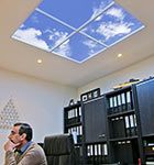 Faux skylights add Full Spectrum lighting to a windowless office!  Elko Ingénierie is a construction engineering firm located just outside of Paris, France. In an effort to make the below-grade offices a little brighter and more comfortable, the firm installed several Luminous SkyCeilings. The virtual skylights provide a very realistic presence of overhead sky. Biophilic elements, such as these illusions of real sky, have proven to promote relaxation and comfort.