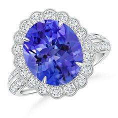 Sculptural and detailed, this statement tanzanite and diamond ring will be the perfect addition to any collection. Handcrafted in 14k white gold, it features a vibrant oval tanzanite of top grade framed in a vintage inspired floral diamond halo with meticulous detailing underneath the mounting. Further, the diamonds on shank create remarkable eternity effect, making this luxury tanzanite ring more desirable.