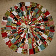 freezeframe: Tutorial: Christmas Tree Skirt Easier than it looks - wedge ruler and 140 charm squares (sewn into strips then cut into wedges, flip and sew back together)