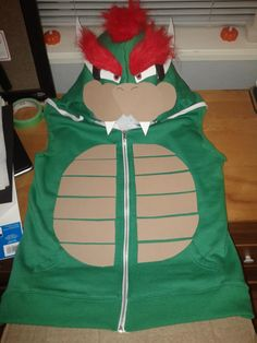 Made this (no sewing required) Bowser costume out of a hoodie for a Mario themed part. His face is positioned as far forward as possible on the hood.