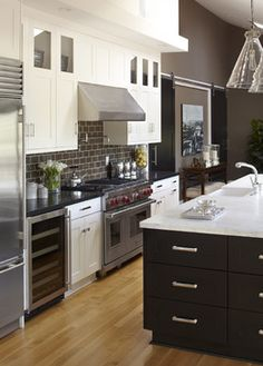 this is interesting:  white cabinets with black tops at perimeter, and black cabinets with white top at island.  Also gives a sense of what charcoal tiles and wall would look like, and I'm kind of digging the island pendants.