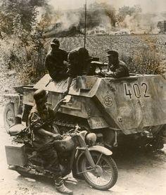 """1944, Un membre de la 11. SS-Freiwilligen- Panzergrenadier-Division """"Nordland"""" tend un document à un SS-Kradschutze (courier à moto) depuis son half-track"""