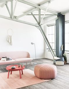 Industrial white living space with metal beams and pink and coral furniture