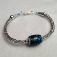 Stainless steel viking knit bracelet with blue and black focal bead, $25