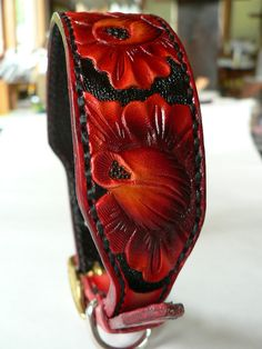 Handmade leather dog collar 8 in vibrant reds on a floral display. Comprised from Hermann Oak leather with a black vintage style interior strap