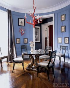 In Jamie Creel and Marco Scarani's Paris home, dramatic, dusky blue walls play up the dining room's round shape and act as the perfect backdrop for Thomas Boog's coral light fixtures.