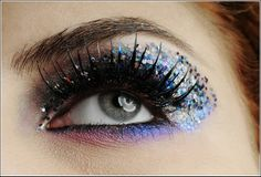 This makeup is done with the help of coarse glitter along the corner of the eye in a mixture of light and dark blue shades and black eyeshadow at the inner side. The look is finished with two eye shadows purple and blue along the lower eye lid and after that thick mascara is applied.