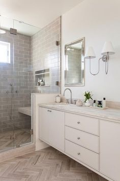 Beside a seamless glass shower fitted with a bench mounted over a taupe herringbone floor and beneath a niche framed by gray stacked wall tiles, a cream floating dual bath vanity boasts satin nickel knobs and a cream stone countertop completed with oval sinks and a satin nickel gooseneck faucets.