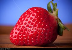 Macro of strawberry on wood table. Rights Managed Exclusive