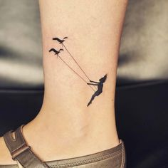 Bird swing tattoo on the ankle.