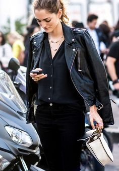 A button-down shirt is paired with motorcycle jacket, black pants, and layered necklaces