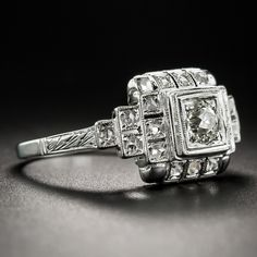 Consummate Art Deco geometry is in full force in this singular and stunning sparkler, dating from the peak of the period - circa 1925. Intricately handcrafted in platinum, the multidimensional mounting centers on a .30 carat European-cut diamond embellished all around with tiny rose-cut diamonds, each set in individual square settings. Delicate milgraining and decorative hand engraving add the finishing touches to this striking, original Jazz Age jewel. The vestige of a personal inscription…