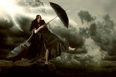 cloaked girl struggling in strong winds
