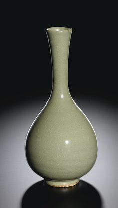 AN EXTREMELY RARE 'LINRU' BOTTLE VASE  SONG DYNASTY  Estimate: 2,000,000 - 3,000,000 HKD   finely potted with an elegant pear-shaped body rising from a narrow cylindrical foot to a tall, slender neck flared toward the rim, covered overall in a rich, evenly crackled pale moss-green glaze stopping just above the footring revealing the brick-red biscuit-fired body, the interior and the recessed base partially glazed    29.5 cm., 11 5/8  in.