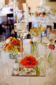 Low mini arrangements of dahlia blossoms and mums with tall stemmed candleholders.