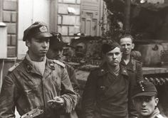 Panzer IV crew from 21.Panzer Division at Rouen, Normandy, France 21/23 August 1944, Boulevard des Belges, just after crosing the Seine River. Panzer officer (left) is wearing a Luftwaffe camo para jump smock with added Skull collar tabs, also cut down for wear in a tank.
