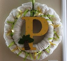 Just unfold a diaper, wrap it around a wreath form, and tie it with a ribbon (I alternated yellow and green).  Attach a long ribbon to the top to hang from the door.  I put a large, scrapbook paper covered letter P in the middle of the wreath and glued a little, wooden palm tree to personalize the project.