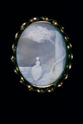 """Oval pin with gold surround trimmed with twisted gold wire. Cameo center is beige shell with cream relief carving of woman standing near a stone wall under a tree. Pin is missing from back of brooch. The name """"Mary Tanouk"""" is scratched on the back of the shell.Probable DateMid-19th century"""