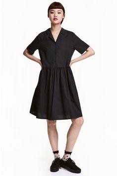 Robe en coton: Robe ample de longueur genou en popeline de coton. Modèle à encolure en V avec col et boutonnage en haut. Manches courtes terminées par revers cousu. Découpe à la taille et jupe froncée.