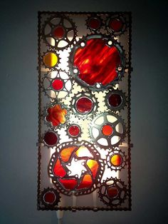 Recycled bicycle cog wall sconce with colored stained glass