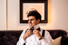 Asian groom getting ready with bow tie