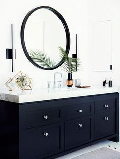 Black painted vanity with thick marble counter and modern sconces