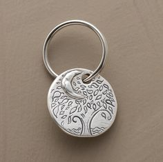 "LOVE BEYOND THE MOON KEYRING -- Jes MaHarry's sky-high oak signifies infinite love. Two-sided pewter disk is handmade in USA. Base metal keyring. Exclusive. 1"" dia.  $48"