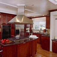 Cabinets with red stain, dark granite and lighter wood tone on floors