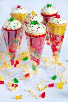 vul een champagne glas met snoep, en zet er vervolgens een cupcakes met vlieg wat room erop op.