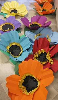 It looks like you accordian fold construction paper, round one edge, overlap 5-6 to form a flower than layer a yellow and black circle in middle where you fringe cut the edges. IMG_4613 by elizabeth williams, via Flickr