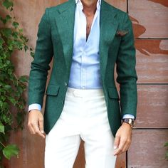 Shop this look on Lookastic: https://lookastic.com/men/looks/blazer-dress-shirt-dress-pants-pocket-square-watch/11900 — Dark Green Blazer — Dark Green Floral Pocket Square — Light Blue Dress Shirt — Beige Dress Pants — Dark Brown Leather Watch