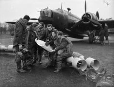 A bomber crew of No. 311 (Czechoslovak) Squadron RAF study a map, while sitting on 250-lb GP bombs which are about to be loaded into their Vickers Wellington Mark IC at East Wretham, Norfolk.