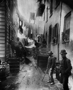 "1887: A group of men loitering in an alley known as ""Bandits' Roost"", situated off Mulberry Street in New York City"