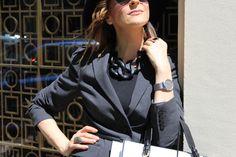 Chaqueta gris, collar negro, melena mido, cinturón negro, gorro en negro,gafas en gris y reloj en plata