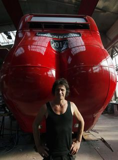 Czech artist David Cerny poses next to a London bus that he has transformed into a robotic sculpture in Prague July 2, 2012.